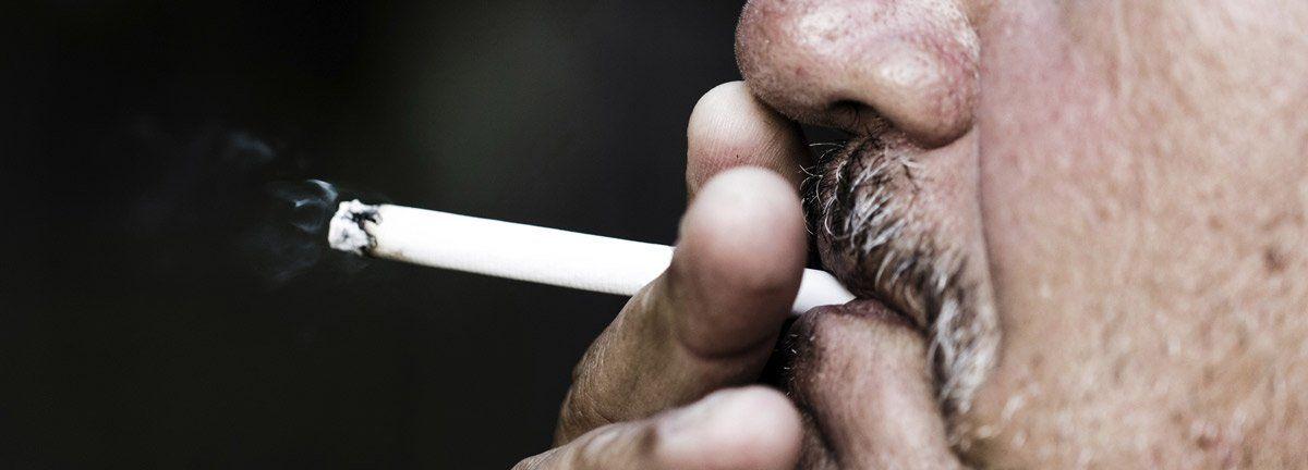 Alter Mann mit Schnurrbart raucht Zigarette und denkt über eine Raucherhypnose, einen Rauchstopp mit Hypnose nach.