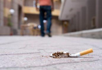 zertretende Zigarette am Straßen Boden nach einer Raucherentwöhnung durch Hypnose von einem neu geborenen Nichtraucher durch Hypnose