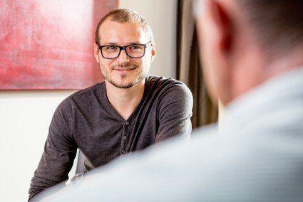 Klient sitzt dem Hypnotiseur Udo Fuchs gegenüber und hört ihm interessiert im Vorgespräch zu
