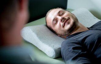 Klient liegt absolut entspannt auf der Hypnoseliege und lächelt