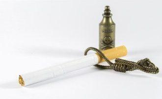 Zigarette mit Galgenstrick und Totenkopf als Symbol der Rauchsucht liegen auf einem weißen Tisch - die Raucherhypnose kann Sie schützen und durch Hypnose rauchfrei werden lassen.