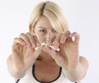 Frau zerbricht, nachdem Sie in Hypnose zum Nichtraucher geworden ist, mit beiden Händen eine Zigarette. Sie ist nun Rauchfrei in Hypnose geworden nach einer gelungenen Raucherentwöhnung.
