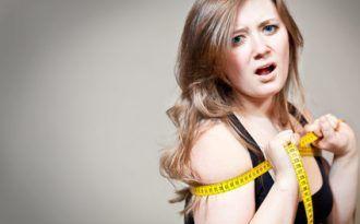 Frau mit Maßband um den Körper gewickelt ist verzweifelt über ihre Figur und den JoJo Effekt