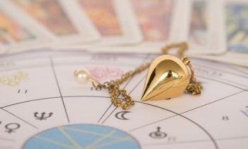 goldenes Pendel liegt auf einem Pentagramm