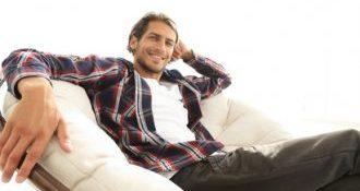 Mann liegt relaxed im Sessel und freut sich auf die Hypnose Sitzung