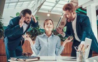 Frau sitzt total entspannt am Schreibtisch zwischen zwei Männern, die auf sie einreden.