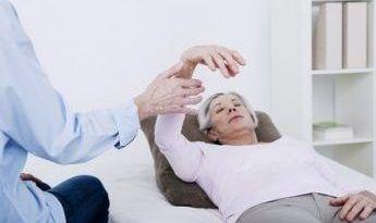 Armlevitation in Fuchs-Hypnose bei einer älteren Frau die auf einer Hypnoseliege liegt