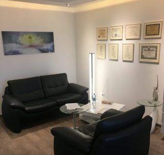 Besprechungsecke des Fuchs Hypnose Studio in Bad Saulgau mit Sessel im Vordergrund und Sofa im Hintergrund, an den Wänden Fuchs-Hypnose Zertifikate