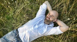 Mann liegt relaxed nach einer Fuchs-Hypnose Sitzung im Gras und hat die Hände hinter dem Kopf verschränkt und lächelt glücklich