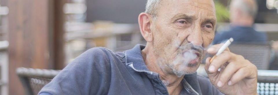 Alter Mann raucht Zigarette und bläst den Rauch aus dem Mund