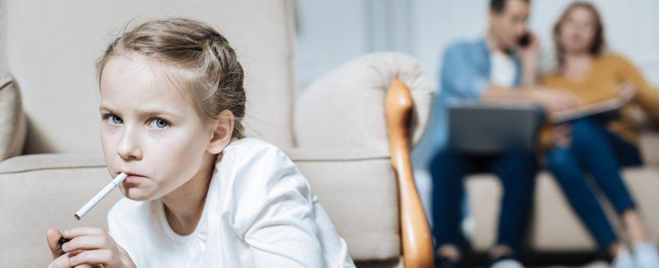 Kleines Mädchen raucht im Vordergrund Zigarette mit den Eltern im Hintergrund auf einem Sofa