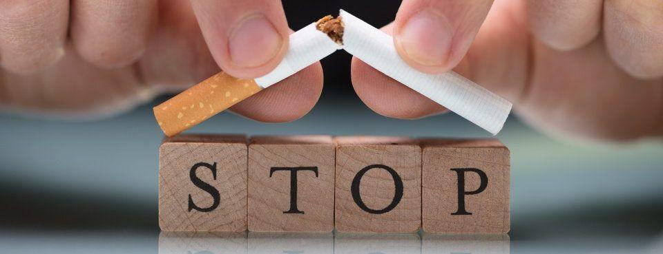 Mann zerbricht Zigarette vor einem Schild mit Rauchstopp mit Hypnose als Symbol für eine Raucherentwöhnung bei Udo Fuchs-Hypnose.