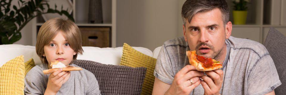 Vater und Sohn essen jeden Tag Pizza beim Fernsehen