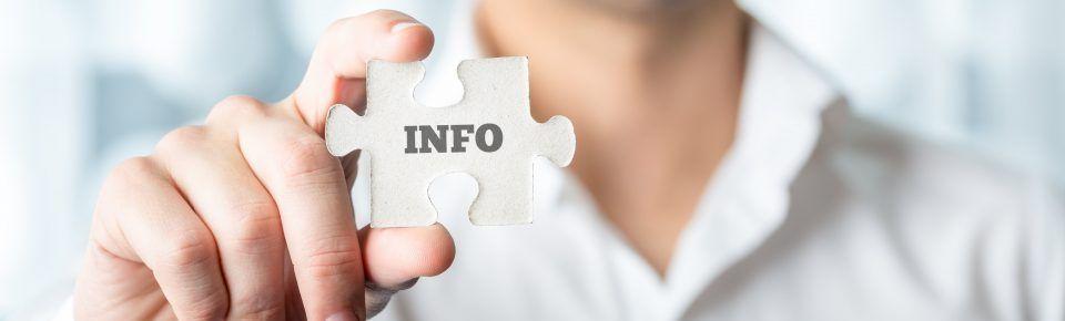 Mann hält ein Puzzlestück mit der Aufschrift Info in den Händen