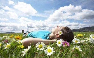 Frau liegt schlafend in einer Blumenwiese nach einer Hypnose-Sitzung