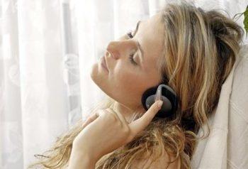 Frau mit Kopfhörer ehnt sich an Sessel an, im Hintergrund ein Vorhang und geniesst die Fuchs-Hypnose
