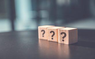 3 Holz-Wuerfel mit Fragezeichen auf einem Tisch als Symbol dass niemand in Hypnose willenlos ist
