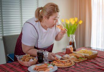 Frau steht an einem Tisch und stopft Essen in sich hinein - aufgenommen vor dem abnehmen mit Hypnose