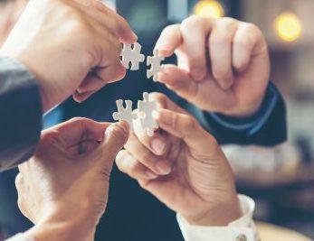 Vier Hände Zeigen Puzzle Stücke in die Kamera als Symbol, dass in einer Hypnosesitzung Teamwork die Voraussetzung für den Erfolg ist.