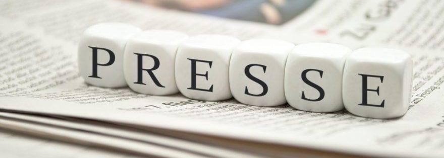 Würfel liegen auf einer Zeitung mit der Aufschrift Presse