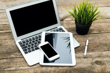 Verschiedene Computer, Laptop, Smartphone liegen auf einem brauen Tisch mit einer grünen Pflanze - mehr benötigt man für eine Hypnose Online Sitzung nicht