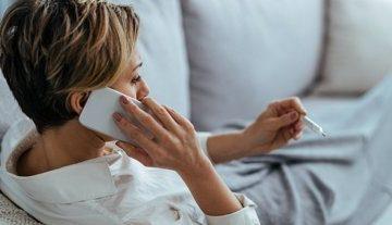Frau beim Fiebermessen mit Fieber sagt die Hypnosesitzung ab.