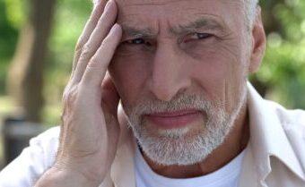 Älterer Mann hält die Hand an seinen Kopf ist verzweifelt weil er nicht mit dem Rauchen aufhören kann.