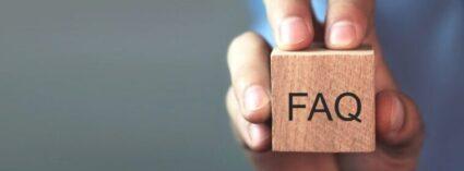 Mann zeigt FAQ Symbol über Hypnose auf einem Holzwürfel
