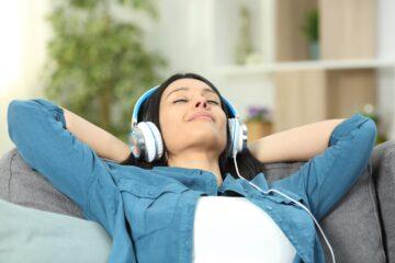 Frau mit Armen hinterm Kopf verschränkt und Kopfhörern relaxt zurückgelehnt auf dem Sofa und geniesst die Fuchs-Online-Hypnose