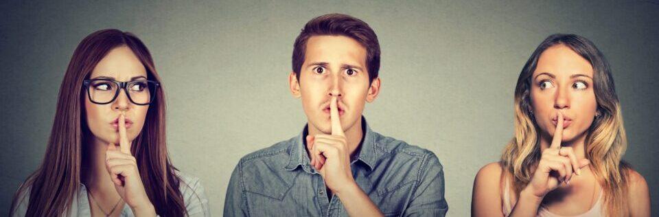2 Frauen und ein Mann mit dem Finger an den Lippen hüten das Geheimnis der Hypnose