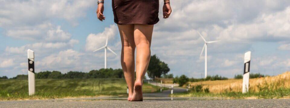 Beine einer Frau laufen auf einer einsamen Landstrasse als Symbol, dass der erste Schritt zum Abnehmen im Kopf beginnt.