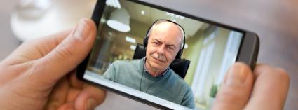2 Hände halten ein Smartphone mit einer im Display sichtbaren Online Hypnose Sitzung mit Hypnotiseur Udo Fuchs • Online-Hypnose wirksam wie eine Studio Sitzung