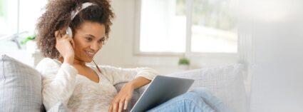 Junge Frau mit Laptop bei Online-Video-Sprechstunde • Online-Hypnose wirksam wie eine Studio Sitzung